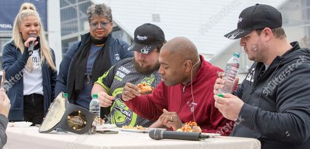 Stock Picture of From left, Emcee Nikky Williams and Sherri Williams watch as the Johnsonville Tailgate Throwdown judges Trevor Morris, Shaun Alexander and Mello sample one of the dishes on in Atlanta