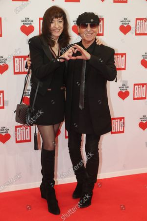 Stock Photo of Klaus Meine (R) of the band 'Scorpions' and his wife Gabi (L) pose for the media on the red carpet of the 'Ein Herz Fuer Kinder' (lit: A Heart for Children) gala show in Berlin, Germany, 07 December 2019. German television channel ZDF and newspaper 'Bild' with their charity even collect donations for children's charity organizations in Germany and the whole world.