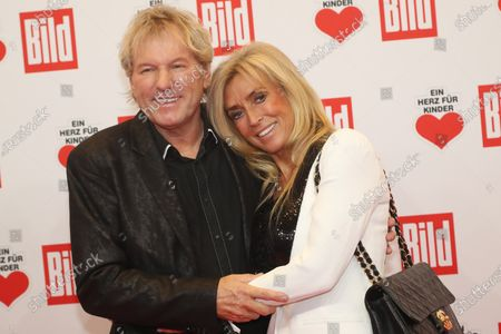 Stock Image of Bernhard Brink (L) and his wife Ute (R) pose for the media on the red carpet of the 'Ein Herz Fuer Kinder' (lit: A Heart for Children) gala show in Berlin, Germany, 07 December 2019. German television channel ZDF and newspaper 'Bild' with their charity even collect donations for children's charity organizations in Germany and the whole world.