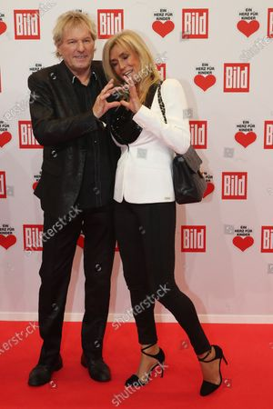 Stock Photo of Bernhard Brink (L) and his wife Ute (R) pose for the media on the red carpet of the 'Ein Herz Fuer Kinder' (lit: A Heart for Children) gala show in Berlin, Germany, 07 December 2019. German television channel ZDF and newspaper 'Bild' with their charity even collect donations for children's charity organizations in Germany and the whole world.