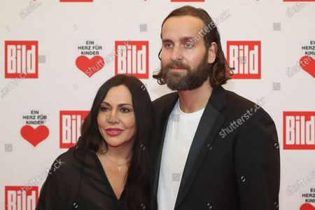 Stock Photo of Simone Thomalla (L) and handball goal keeper Silivio Heinevetter (R) pose for the media on the red carpet of the 'Ein Herz Fuer Kinder' (lit: A Heart for Children) gala show in Berlin, Germany, 07 December 2019. German television channel ZDF and newspaper 'Bild' with their charity even collect donations for children's charity organizations in Germany and the whole world.
