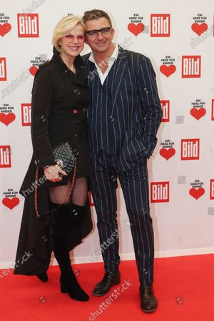 Hans Sigl (R) and his wife Susanne Kemmler (L) pose for the media on the red carpet of the 'Ein Herz Fuer Kinder' (lit: A Heart for Children) gala show in Berlin, Germany, 07 December 2019. German television channel ZDF and newspaper 'Bild' with their charity even collect donations for children's charity organizations in Germany and the whole world.