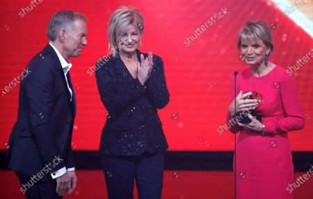 German actress Uschi Glas (R) receives the Golden Heart Award from German TV presenter Carmen Nebel (C) and Johannes Baptist Kerner (L) during the 'Ein Herz Fuer Kinder' (lit: A Heart for Children) gala show in Berlin, Germany, 07 December 2019. German television channel ZDF and newspaper 'Bild' collected donations for children's charity organizations in Germany and the whole world.