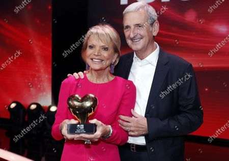German actress Uschi Glas (L) and her husband Dieter Hermann (R) pose with her award after the Ein Herz Fuer Kinder Gala show in Berlin, Germany, 07 December 2019. German television channel ZDF and newspaper 'Bild' collected donations for children's charity organizations in Germany and globally.