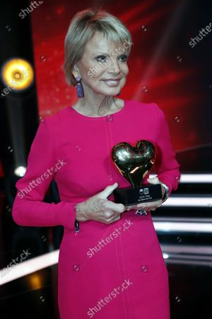 Stock Picture of German actress Uschi Glas poses with her award after the Ein Herz Fuer Kinder Gala show in Berlin, Germany, 07 December 2019. German television channel ZDF and newspaper 'Bild' collected donations for children's charity organizations in Germany and globally.