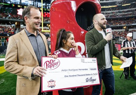 Stock Photo of IMAGE DISTRIBUTED FOR DR PEPPER - Chief Marketing Officer for Keurig Dr Pepper Andrew Springate, left, and host Mike Golic Jr., right, present Jazlyn Rodriguez Hernandez with a $100,000 check at Big 12 Championship thanks to Dr Pepper Tuition Giveaway, in Arlington, Texas
