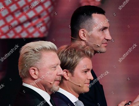 """Former F1 driver Nico Rosberg, center,tennis legend Boris Becker, left, and boxer Wladimir Klitschko, from left, enter the stage during the charity gala """"Ein Herz fuer Kinder"""" (a heart for children) in Berlin, Germany"""