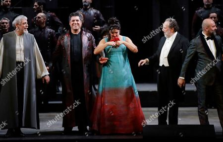"""Russian soprano Anna Netrebko acknowledges the applause of the audience flanked by director Riccardo Chailly, right, and baritone Luca Salsi, at the end of La Scala opera house's gala season opener, Giacomo Puccini's opera """"Tosca"""" at the Milan La Scala theater, Italy, . The season-opener Thursday, held each year on the Milan feast day St. Ambrose, is considered one of the highlights of the European cultural calendar"""