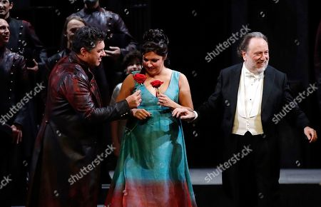 """Russian soprano Anna Netrebko receives red roses from Italian baritone Luca Salsi as they acknowledge the applause of the audience flanked by director Riccardo Chailly, right, at the end of La Scala opera house's gala season opener, Giacomo Puccini's opera """"Tosca"""" at the Milan La Scala theater, Italy, . The season-opener Thursday, held each year on the Milan feast day St. Ambrose, is considered one of the highlights of the European cultural calendar"""