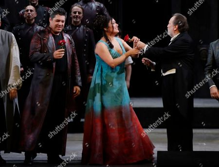 """Russian soprano Anna Netrebko receives a red rose from director Riccardo Chailly as they acknowledge the applause of the audience at the end of La Scala opera house's gala season opener, Giacomo Puccini's opera """"Tosca"""" at the Milan La Scala theater, Italy, . The season-opener Thursday, held each year on the Milan feast day St. Ambrose, is considered one of the highlights of the European cultural calendar"""
