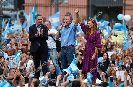 """Argentina's outgoing President Mauricio Macri, center, his running mate Miguel Angel Pichetto, left, and first lady Juliana Awada, acknowledge the crowd during a rally in Buenos Aires, Argentina, . Despite losing to opposition candidate Alberto Fernandez in the recent presidential elections the conservative leader Macri garnered 40 percent of the vote and his """"Let's Change"""" political movement look set to continue being an ongoing force in Argentine politics"""
