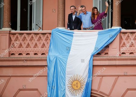 """Argentina's President Mauricio Macri, center, his wife Juliana Awada and his running-mate Miguel Angel Pichetto wave to supporters during a rally in support of Macri, in Buenos Aires, Argentina, . Despite losing to opposition candidate Alberto Fernandez in the recent presidential elections the conservative leader garnered 40 percent of the vote and his """"Let's Change"""" political movement look set to continue being an ongoing force in Argentine politics"""