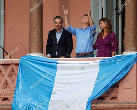 """Argentina's President Mauricio Macri, center, his wife Juliana Awada and his running-mate Miguel Angel Pichetto stand on the balcony of the Casa Rosada executive mansion, during a rally in support of Macri, in Buenos Aires, Argentina, . Despite losing to opposition candidate Alberto Fernandez in the recent presidential elections the conservative leader garnered 40 percent of the vote and his """"Let's Change"""" political movement look set to continue being an ongoing force in Argentine politics"""