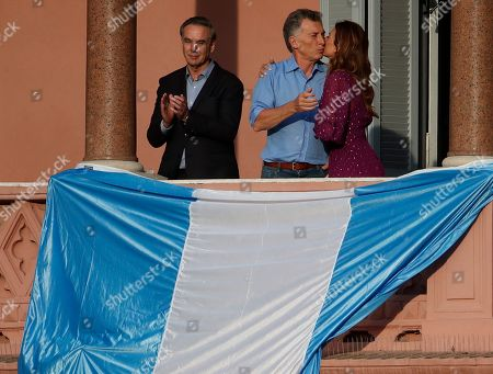 """Stock Picture of Argentina's President Mauricio Macri and his wife Juliana Awada kiss beside his former running-mate Miguel Angel Pichetto react during a rally in support of Macri, in Buenos Aires, Argentina, . Despite losing to opposition candidate Alberto Fernandez in the recent presidential elections the conservative leader garnered 40 percent of the vote and his """"Let's Change"""" political movement look set to continue being an ongoing force in Argentine politics"""