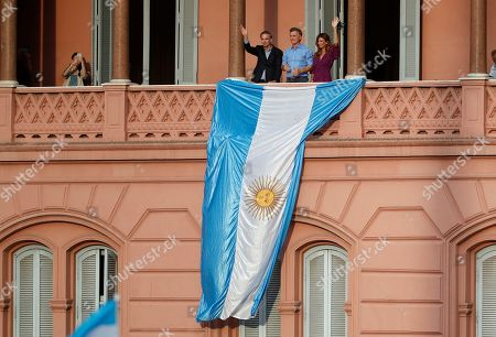 """Stock Photo of Argentina's President Mauricio Macri, center, his wife Juliana Awada and his former running-mate Miguel Angel Pichetto wave to supporters during a rally in support of Macri, in Buenos Aires, Argentina, . Despite losing to opposition candidate Alberto Fernandez in the recent presidential elections the conservative leader garnered 40 percent of the vote and his """"Let's Change"""" political movement look set to continue being an ongoing force in Argentine politics"""