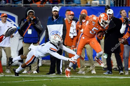 Stock Picture of Clemson wide receiver Tee Higgins (5) breaks a tackle attempt by Virginia cornerback Nick Grant during the first half of the Atlantic Coast Conference championship NCAA college football game in Charlotte, N.C., . Higgins scored on the play