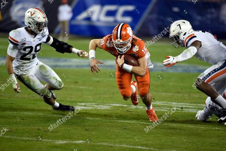 Clemson quarterback Trevor Lawrence (16) runs between Virginia safety Joey Blount (29) and Virginia safety Chris Moore (7) during the first half of the Atlantic Coast Conference championship NCAA college football game in Charlotte, N.C