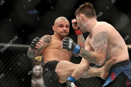 Tim Means, right, absorbs a kick from Thiago Alves during their mixed martial arts bout at UFC Fight Night, in Washington, D.C. Means won via 1st round submission