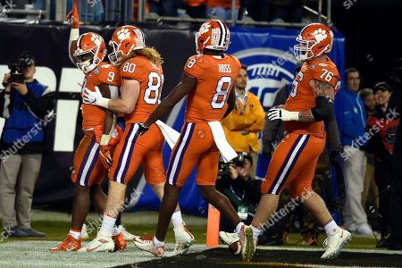 Clemson running back Travis Etienne (9) is congratultaed folwoing his touchdown against Virginia by Clemson tight end Luke Price (80), wide receiver Justyn Ross (8) and offensive lineman Sean Pollard (76) during the first half of the Atlantic Coast Conference championship NCAA college football game in Charlotte, N.C