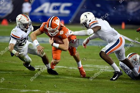 Clemson quarterback Trevor Lawrence (16) runs the ball between Virginia safety Joey Blount (29) and safety Chris Moore (7) during the first half of the Atlantic Coast Conference championship NCAA college football game in Charlotte, N.C