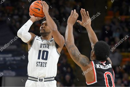 Stock Picture of Utah State forward Alphonso Anderson (10) shoots as Fresno State guard New Williams (0) defends during the first half of an NCAA college basketball game, in Logan, Utah