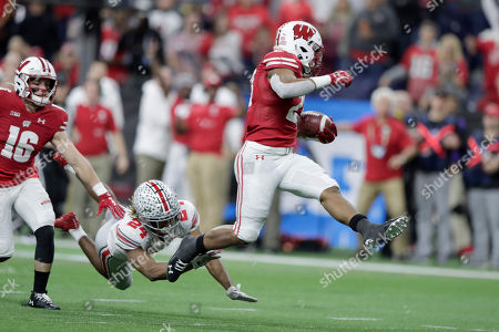 Stock Picture of Wisconsin running back Jonathan Taylor, right, leaps past Wisconsin cornerback James Williams on his way to a touchdown during the first half of the Big Ten championship NCAA college football game, in Indianapolis
