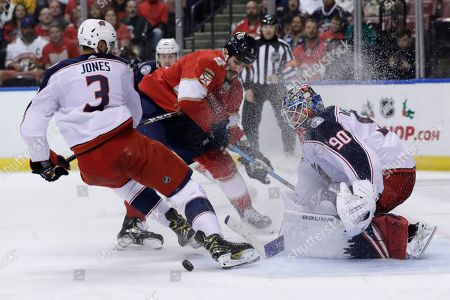Elvis Merzlikins, Seth Jones, Brian Boyle. Columbus Blue Jackets goaltender Elvis Merzlikins (90) defends the goal as Blue Jackets defenseman Seth Jones (3) and Florida Panthers center Brian Boyle (9) fight for the puck during the second period of an NHL hockey game, in Sunrise, Fla