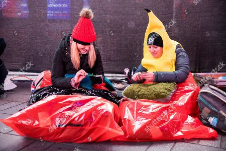 Stock Photo of Lisa Kelly, right, and Leana Shishakova play a card game as they sit in sleeping bags during The World's Big Sleep Out, in New York