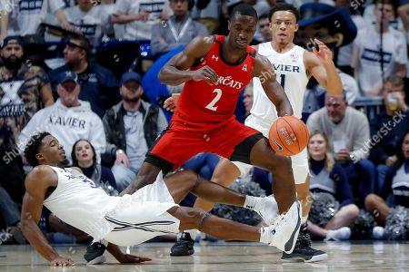 Keith Williams, Quentin Goodin. Cincinnati's Keith Williams (2) fouls Xavier's Quentin Goodin (3) during the second half of an NCAA college basketball game, in Cincinnati