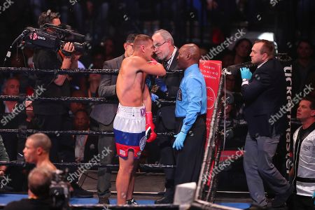 Stock Image of Matvey Korobov retreats to corner with hurt left shoulder during round 2 of a boxing match against Chris Eubank, Jr., in Brooklyn. Eubank won by TKO