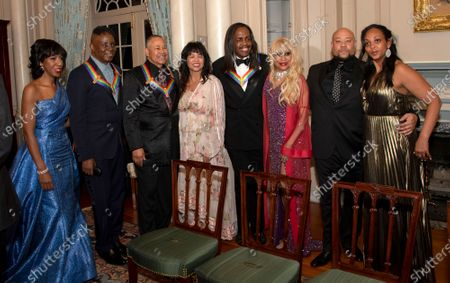 Members of the band Earth, Wind & Fire pose with their spouses, from left to right, Valerie Bailey, singer Philip Bailey, percussionist Ralph Johnson, Susan Johnson, bassist Verdine White, and his wife, Shelly Clark, three of the recipients of the 42nd Annual Kennedy Center Honors, pose with Kahbran White, son of Maurice White and a guest following a dinner at the United States Department of State in Washington, D.C.
