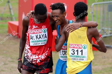 Stock Picture of Third placed Yemaneberhan Crippa of Italy, center, embraces second placed Aras Kaya of Turkey, left, and winner Robel Fsiha of Sweden after finishing the Men's race during the European Cross Country Championships at the Bela Vista park in Lisbon