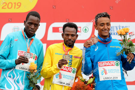 Second placed Aras Kaya of Turkey, winner Robel Fsiha of Sweden and third placed Yemaneberhan Crippa of Italy, from left to right, pose on the podium of the Men's race during the European Cross Country Championships at the Bela Vista park in Lisbon