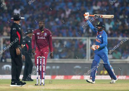 Stock Photo of Ravindra Jadeja, Kesrick Williams. India's Ravindra Jadeja, right, reacts after being dismissed by West Indies' Kesrick Williams, center, during the second Twenty20 international cricket match between India and West Indies in Thiruvanathapuram, India