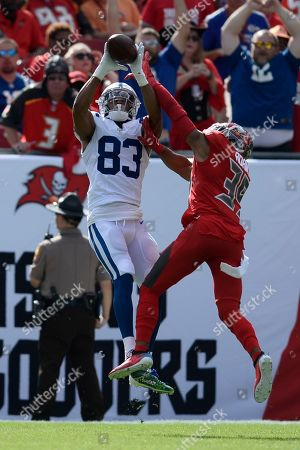 Indianapolis Colts wide receiver Marcus Johnson (83) pulls in a 46-yard touchdown reception in front of Tampa Bay Buccaneers strong safety Andrew Adams (39) during the first half of an NFL football game, in Tampa, Fla