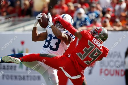 Indianapolis Colts wide receiver Marcus Johnson (83) pulls in a 46-yard touchedown reception in front of Tampa Bay Buccaneers strong safety Andrew Adams (39) during the first half of an NFL football game, in Tampa, Fla