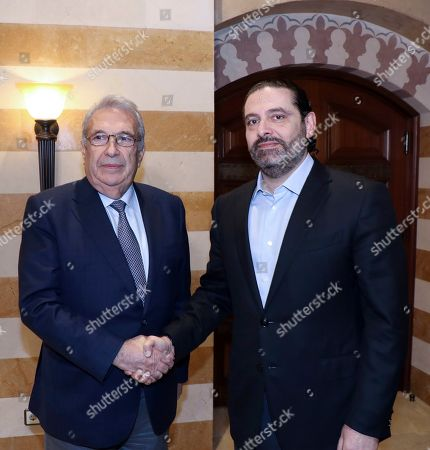 In this photo released by the Lebanese Government, Lebanon's outgoing Prime Minister Saad Hariri, right, shakes hand with Samir Khatib, the head of a major contracting and construction and once considered a favorite candidate for the post of Prime Minister, in Beirut, Lebanon