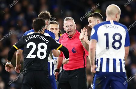 Players speak to referee Jon Moss during a VAR decision.