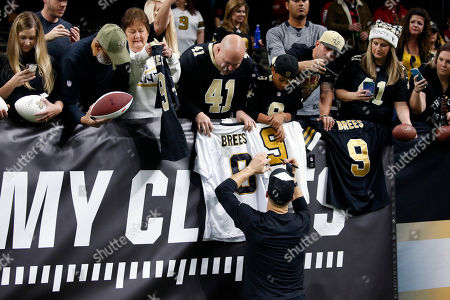 New Orleans Saints quarterback Drew Brees signs autographs for fans in front to a My Cause, My Cleats banner before an NFL football game against the San Francisco 49ers in New Orleans