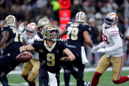 New Orleans Saints quarterback Drew Brees (9) scrambles as he throws a touchdown reception in the first half an NFL football game against the San Francisco 49ers in New Orleans