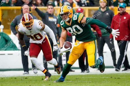 Green Bay Packers' Jimmy Graham runs past Washington Redskins' Landon Collins after a catch during the first half of an NFL football game, in Green Bay, Wis