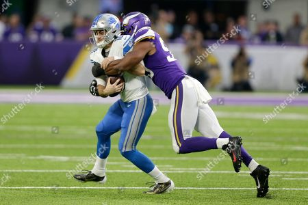 Detroit Lions quarterback David Blough is sacked by Minnesota Vikings defensive end Danielle Hunter, right, during the first half of an NFL football game, in Minneapolis