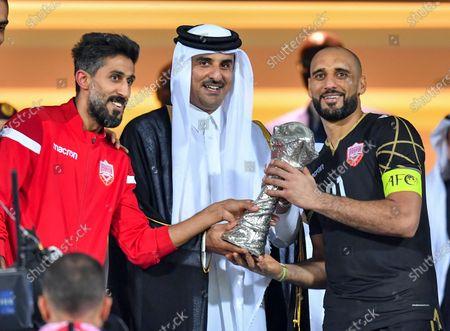 Goalkkeper and captain Sayed Jaffer (R) of Bahrain receives the Gulf Cup trophy from Qatar Emir Sheikh Tamim bin Hamad al-Thani (C) after the 24th Arabian Gulf Cup final soccer match between Bahrain and Saudi Arabia at the Abdullah bin Khalifa Stadium in Doha, Qatar, 08 December 2019.