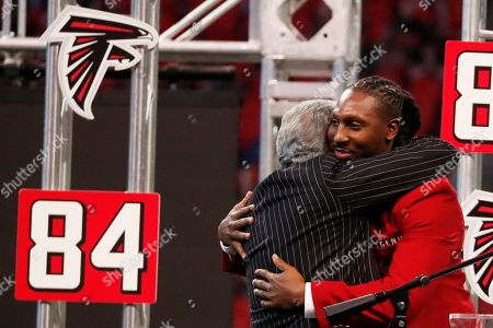 Stock Photo of Former Atlanta Falcons player Roddy White is embraced by Atlanta Falcons Owner Arthur Blank during half time of an NFL football game between the Atlanta Falcons and the Carolina Panthers, in Atlanta