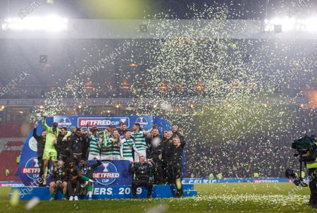 Stock Picture of Strong wind blows green and white confetti behind the Celtic team as Celtic captain Scott Brown lifts the Betfred Cup with team mates on the winner's podium