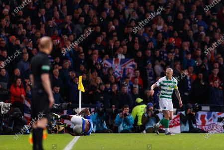 Celtic captain Scott Brown looks back at Alfredo Morelos of Rangers laying on the pitch after Brown appeared to kick Morelos