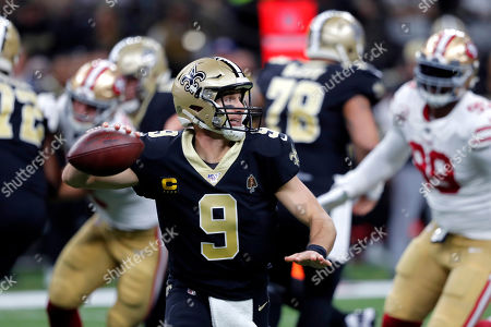 Stock Image of New Orleans Saints quarterback Drew Brees (9) scrambles as he throws a touchdown pass in the first half an NFL football game against the San Francisco 49ers in New Orleans