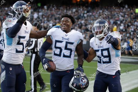 Tennessee Titans inside linebacker Jayon Brown (55) celebrates with inside linebacker Rashaan Evans (54) and inside linebacker Wesley Woodyard (59) after scoring against the Oakland Raiders during the second half of an NFL football game in Oakland, Calif