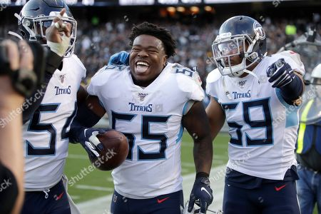 Tennessee Titans inside linebacker Jayon Brown (55) celebrates with inside linebacker Wesley Woodyard (59) after scoring against the Oakland Raiders during the second half of an NFL football game in Oakland, Calif
