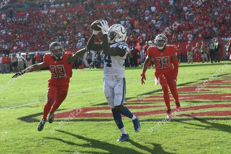 Indianapolis Colts wide receiver Zach Pascal (14) catches a pass for a score as Tampa Bay Buccaneers cornerback Carlton Davis (33) and strong safety Andrew Adams (39) defend during the second half of an NFL football game, in Tampa, Fla